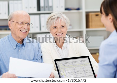 Smiling senior couple meeting with a broker in her office sitting close together holding paperwork and listening to her speak