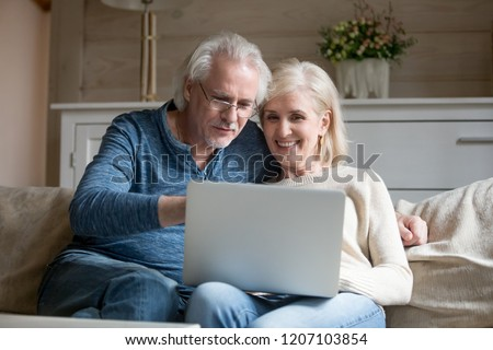 Smiling senior couple sit on couch hugging using laptop, happy aged husband and wife relax on sofa at home watching video or shopping online at computer together. Elderly and technology concept