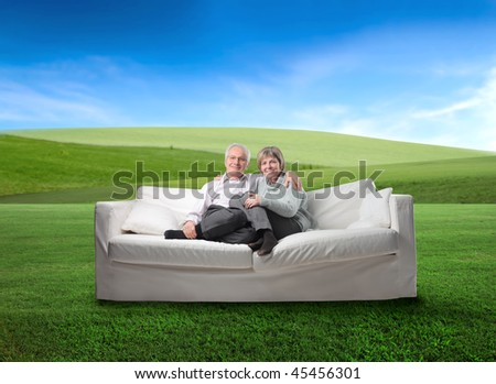 Smiling senior couple sitting in a couch in the middle of a green meadow