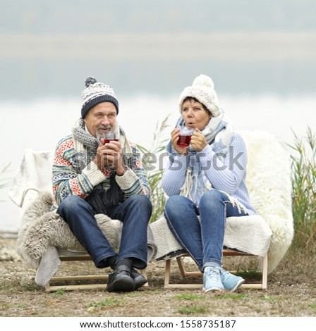 smiling senior couple sitting on the winter beach in warm blanket chair and drinking hot tea stock photo