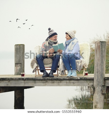 smiling senior couple sitting on the winter beach in warm blanket chair and reading a book stock photo