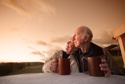 Smiling senior couple sitting outside at sunset