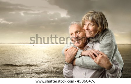 Smiling senior couple standing at the seaside at sunset
