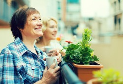 Smiling senior female friends staying on balcony with cup of coffee in hands