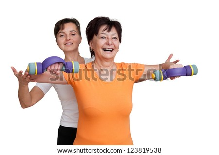 Smiling senior fitness woman exercising with barbells assisted by coach - isolated on white
