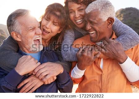 Smiling Senior Friends Having Fun Walking In Countryside Together Stock fotó ©