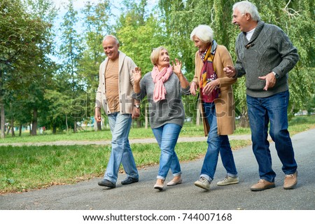 Smiling senior friends wearing knitted sweaters and cardigans walking along park alley and chatting animatedly with each other, picturesque view on background stock photo