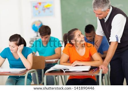 smiling senior high school teacher talking to student in classroom