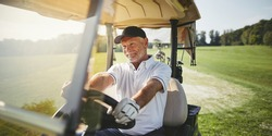 Smiling senior man driving a golf cart along a fairway while playing a round of golf on a sunny day