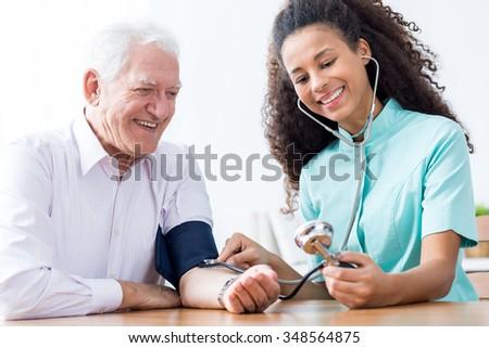 Smiling senior man having measured blood pressure