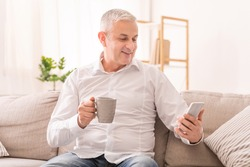 Smiling Senior Man Having Rest Using Smartphone And Drinking Coffee Or Tea, Sitting On Sofa At Home, Copyspace