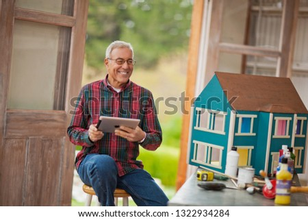 Smiling senior man holding an iPad while sitting in a garage next to a dolls house.