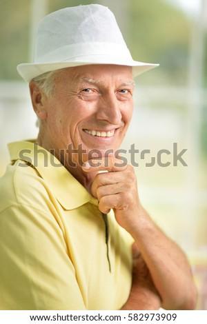 smiling senior man in hat  #582973909