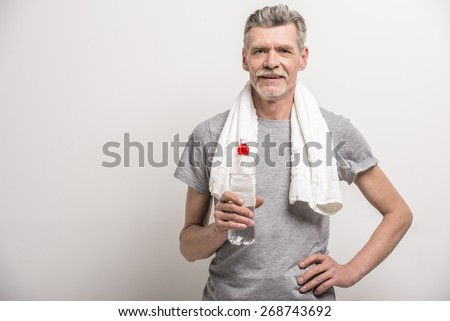 Smiling senior man in T-shirt on neck towel with bottle water on grey background. Stock photo ©