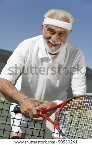 Smiling senior Man leaning on tennis net, holding tennis racket
