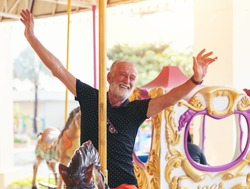Smiling senior man on horse carousel ride at the amusement theme park, male senior tourist, elderly man having fun, relaxing at the theme park. people, tourist and holiday concept