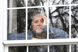 Smiling senior man standing at the window looking out during quarantine