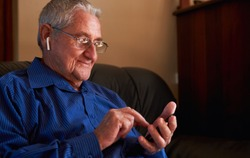 Smiling senior man using smart phone sat on sofa