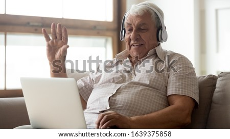 Smiling senior man wear earphones wave to camera having video call on laptop, happy elderly male in headphones sit on couch at home talk using modern technologies and wireless connection