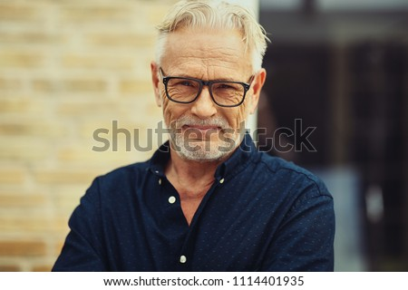 Smiling senior man with a beard and wearing glasses standing by himself outside in front of his home