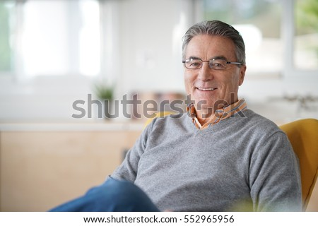 Smiling senior man with eyeglasses relaxing in armchair #552965956