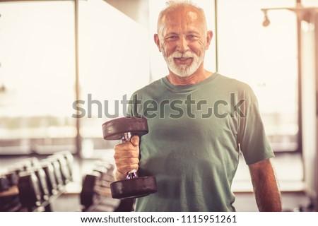 Smiling senior man with weight at gym. Looking at camera.