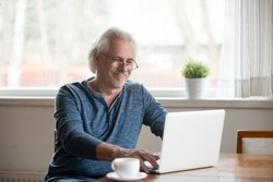 Smiling senior middle aged man in glasses working on laptop at home, happy elderly mature male user looking at computer screen communicating online or using software for dating, reading morning news