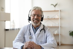 Smiling senior old doctor wears headset looking at camera. Remote online medical chat consultation, tele medicine distance services, virtual physician conference call, telemedicine concept. Portrait.