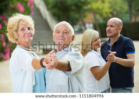 Smiling senior parents with adult children dancing in summer park
