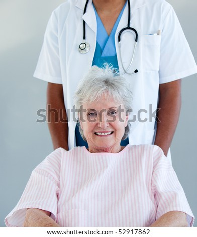 Smiling senior patient sitting on a wheelchair in a hospital