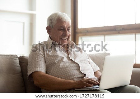 Smiling senior 70s man sit relax on sofa in living room browsing internet on modern computer gadget, happy mature 80s grandfather rest on couch at home watch video surf wireless web on laptop