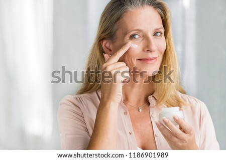 Smiling senior woman applying anti-aging lotion to remove dark circles under eyes. Happy mature woman using cosmetic cream to hide wrinkles below eyes. Lady using day moisturizer. #1186901989