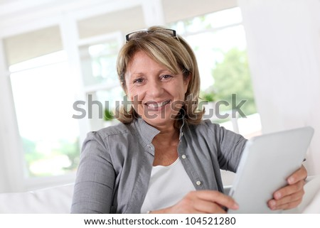Smiling senior woman at home connected on internet