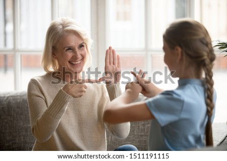 Smiling senior woman grandmother make sign language talk gesturing with granddaughter at home, deaf dumb mute grandparent and grandchild speak using nonverbal communication, disabled people concept