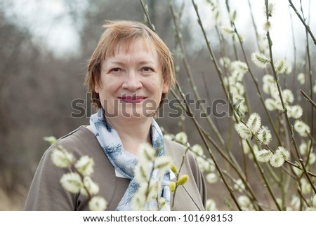 Smiling senior woman  in spring willow twig with buds outdoor