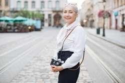 Smiling senior woman in stylish clothes holding retro photo camera while standing outdoors. City street on blurred background. Active lady on retirement.
