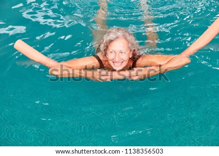 Smiling senior woman in the swimming pool is doing aqua fitness with buoyancy aid