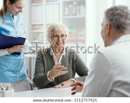 Smiling senior woman talking with the doctor in his office, a nurse is standing next to her: medical assistance and healthcare concept Stockfoto ©