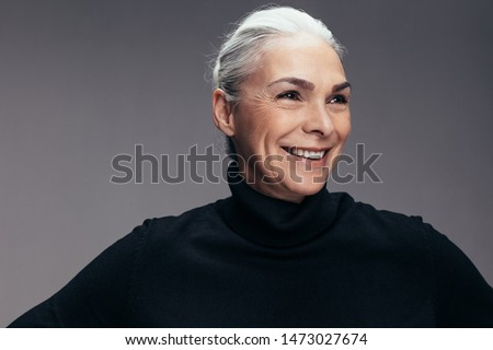Smiling senior woman wearing black t-shirt and looking away. Mid adult caucasian female in casuals on grey background.