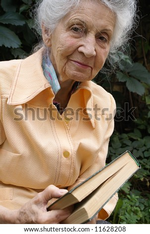 Smiling senior woman with book on green leaves background