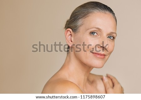Smiling senior woman with bun hair and hand on naked shoulder. Portrait of beauty mature woman isolated over grey background with copy space looking at camera. Body and skin care concept.