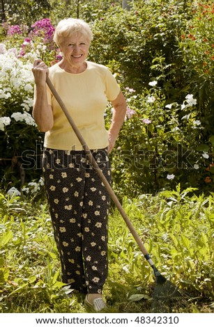 Smiling senior woman with rake in the garden