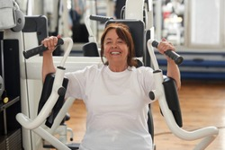 Smiling senior woman working out at gym. Healthy elderly woman exercising using chest press machine at fitness club. Active way of life.
