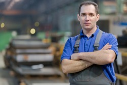 Smiling service man worker with folded arms at factory workshop machine background