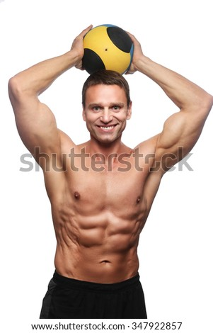 Smiling shirtless bodybuilder posing with valleyball. Isolated on white background.
