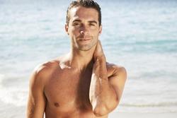 Smiling shirtless handsome man on beach, portrait