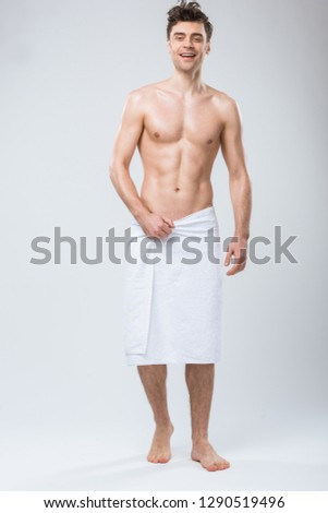 smiling shirtless man posing in towel isolated on grey