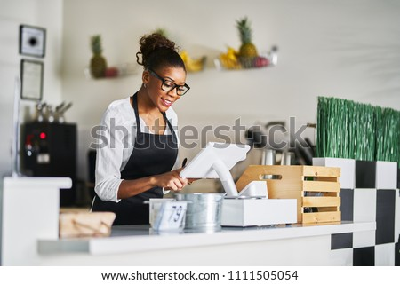 smiling shop assistant using pos point of sale temrinal to put in order from notepad at restaurant register