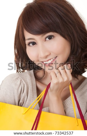 Smiling shopping woman of Asian holding bags and looking at you.
