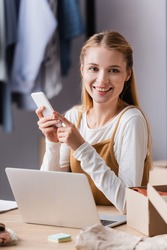 smiling showroom proprietor holding mobile phone near laptop on blurred foreground